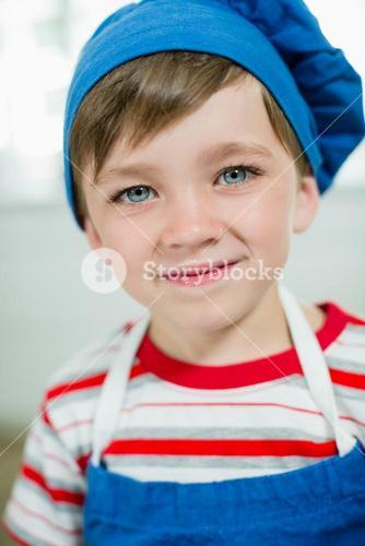 Portrait of cute boy in chef hat and apron
