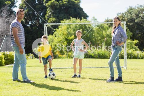 Family playing football together at the park