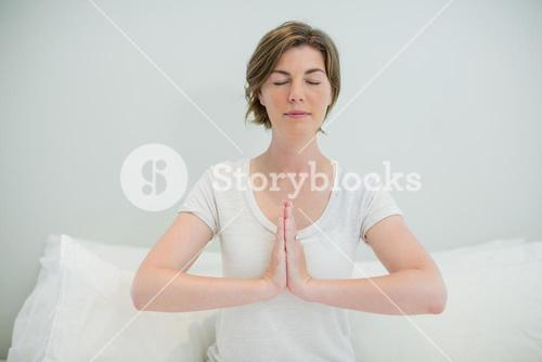 Woman doing meditation on bed in bedroom