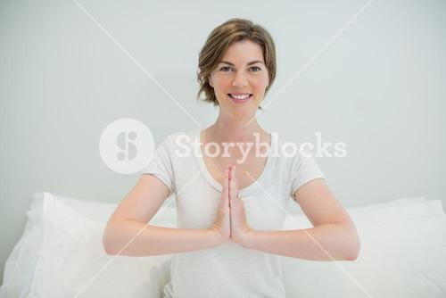 Smiling woman doing meditation on bed in bedroom at home