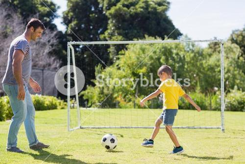 Father and son playing football in the park