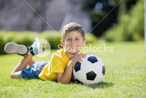 Boy lying on grass with football in the park