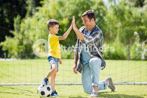 Father and son giving high five in the park