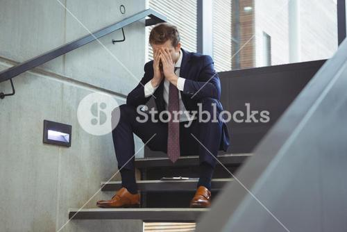 Depressed businessman sitting on stairs
