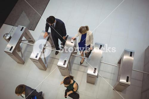 Business executives passing through turnstile gate