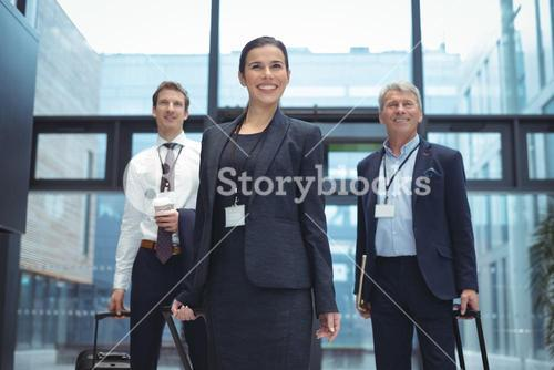 Business executives with trolley bag standing