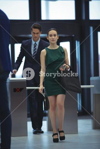 Businesswoman passing through turnstile gate