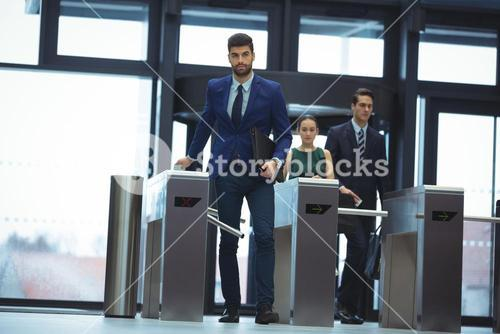 Businessman passing through turnstile gate