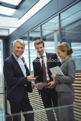Businesspeople discussing over electronic devices in the passageway