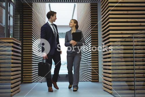 Business executives walking in corridor
