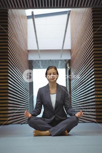 Businesswoman performing yoga in the corridor