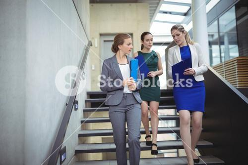 Businesspeople interacting with each other while walking downstairs