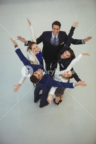 Businesspeople standing together with arms outstretched