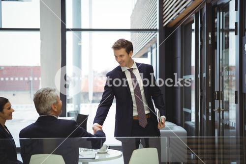 Businesspeople shaking hands in a lobby