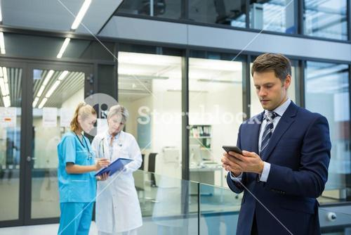 Businessman using mobile while doctor and nurse discussing over clipboard in background