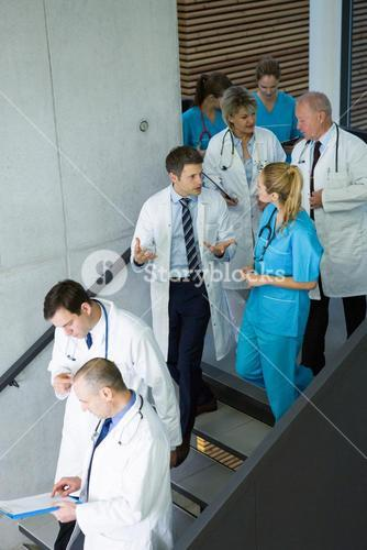 Group of doctors and surgeons interacting with each other on staircase