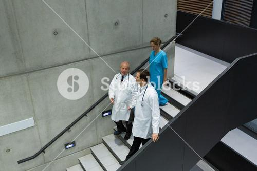 Doctors and surgeons interacting with each other on staircase