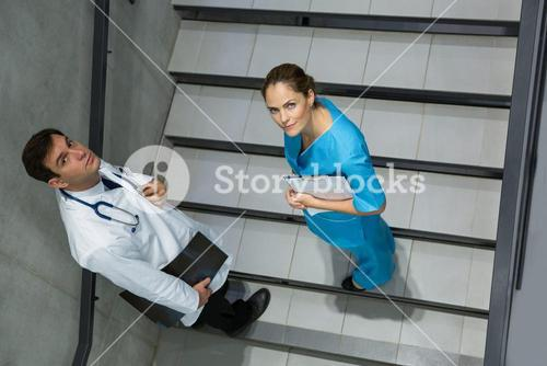 High angle view of doctor and surgeon standing together on staircase