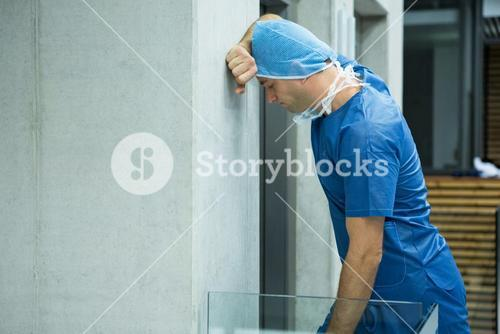 Tensed male surgeon leaning on wall near elevator