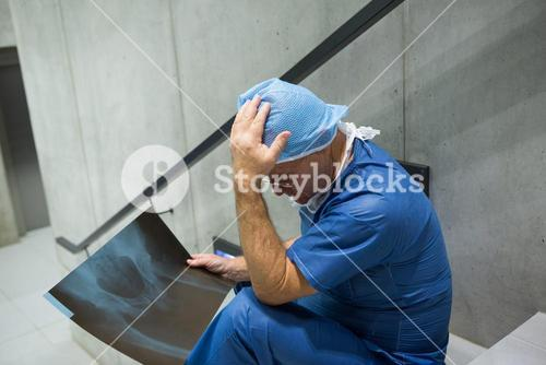 Tensed male surgeon examine x-ray on staircase