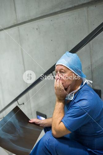 Worried male surgeon holding x-ray on staircase