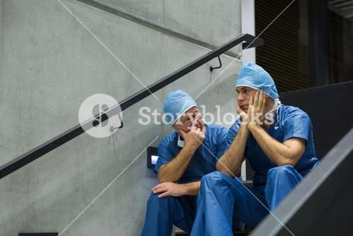 Worried male surgeons sitting on staircase