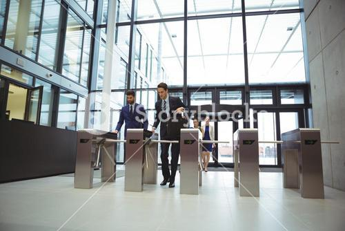 Businesspeople scanning their cards at turnstile gate