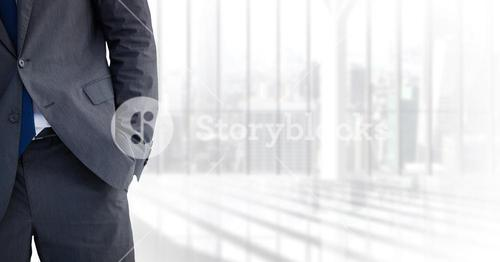 Business man mid section with hand in pocket against blurry window