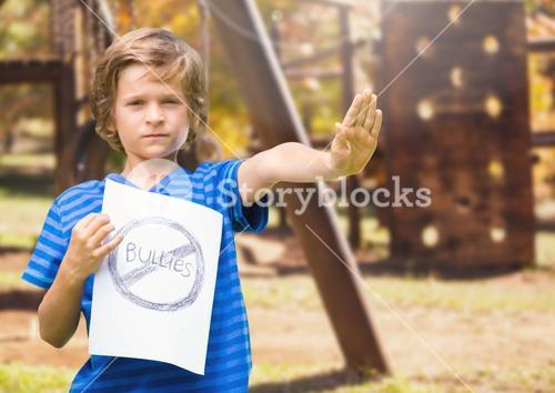 Sad boy holdingn anti bullying sign  against playground