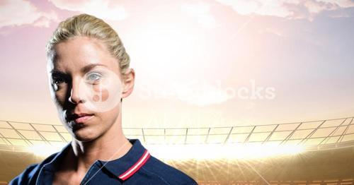 Woman in polo shirt in stadium with bright lights and evening sky