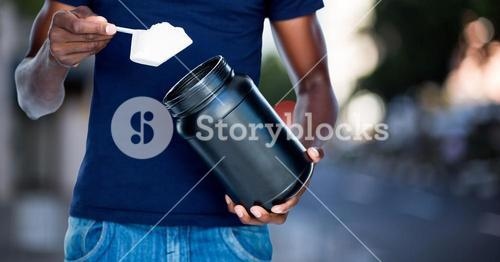 Man taking supplement against blurry street scene