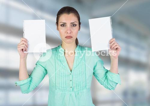 Sad woman holding ripped apart paper against blurred blue background