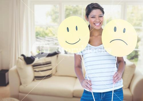Woman holding happy or sad faces in sitting room