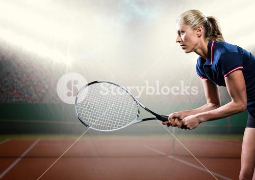 Tennis player with racket outstretched on court with audience and bright lights