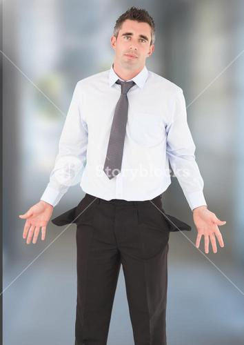 Businessman with empty pockets against blurred background