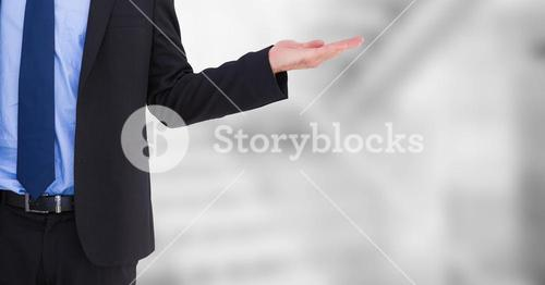 Business man mid section with hand out at side against blurry grey stairs