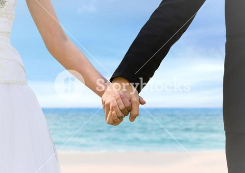Bride and groom holding hands at blurry beach