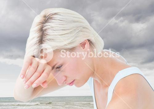 Sad tired woman against cloudy sky and ocean