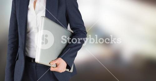 Business woman mid section holding laptop in blurry room