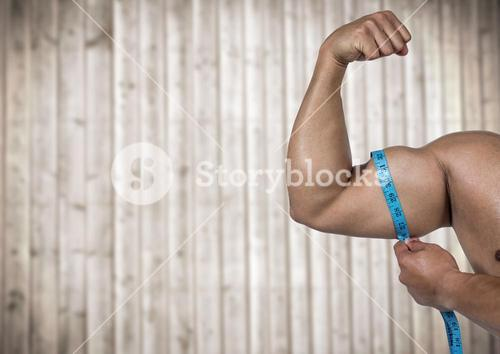 Muscular arm with measuring tape against blurry wood panel