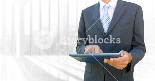 Business man mid section with tablet against blurry window