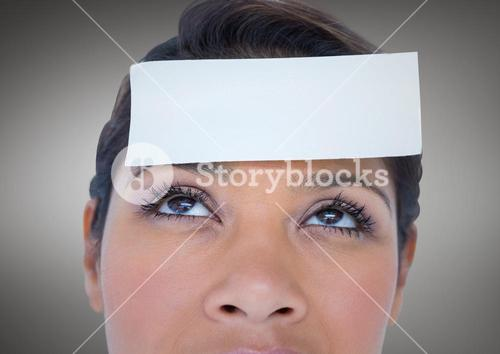 Close up of Woman with card on head against grey background