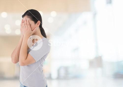 Sad woman grief hands over face against bright background