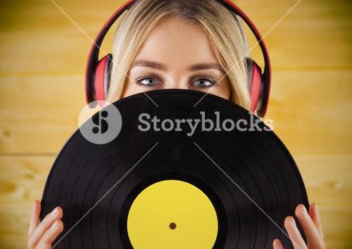Woman with headphones and record against yellow wood panel