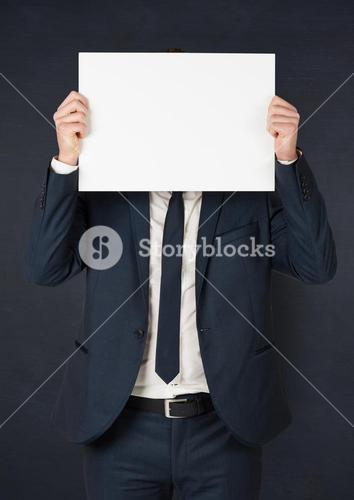 Business man with blank card over face against navy chalkboard