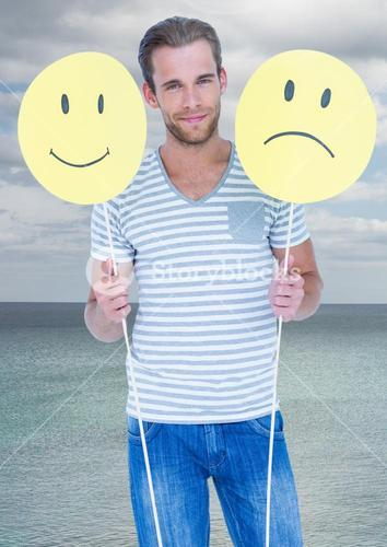 Man holding happy and sad faces against sea