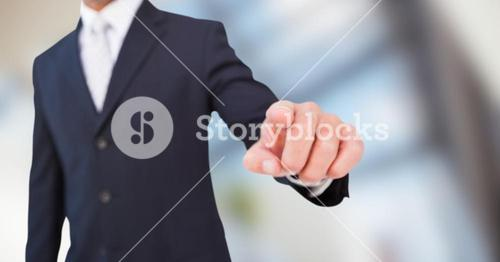 Business man mid section pointing down against blurry window