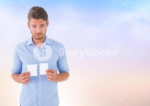 Sad man ripping paper against soft sky