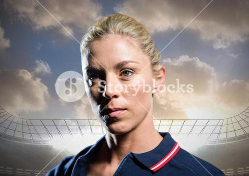 Woman in polo shirt in stadium with bright lights and sky with clouds