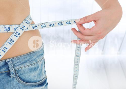 Woman's hip with measuring tape against blurry window